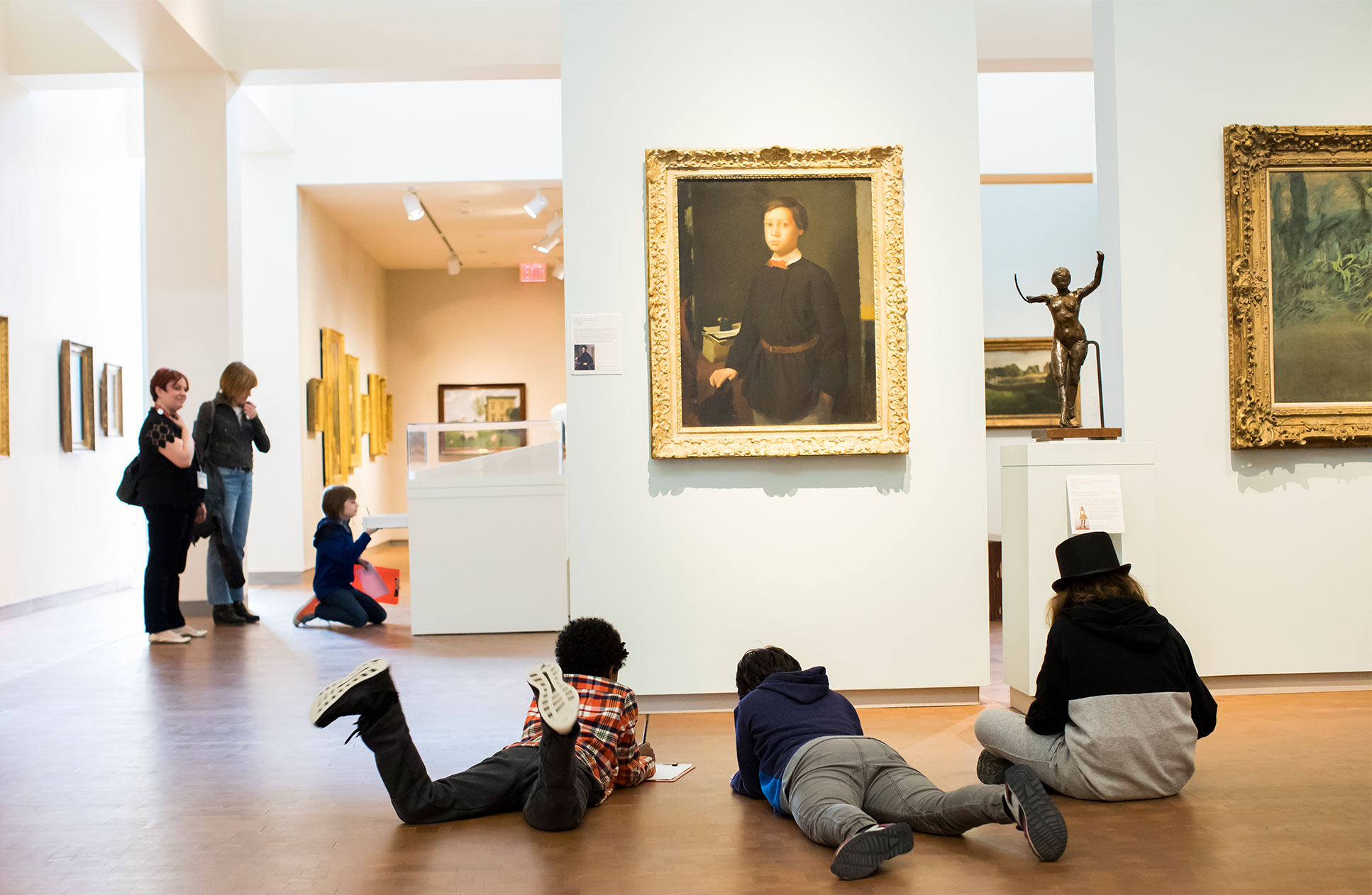 School visitors looking at and drawing art in the galleries