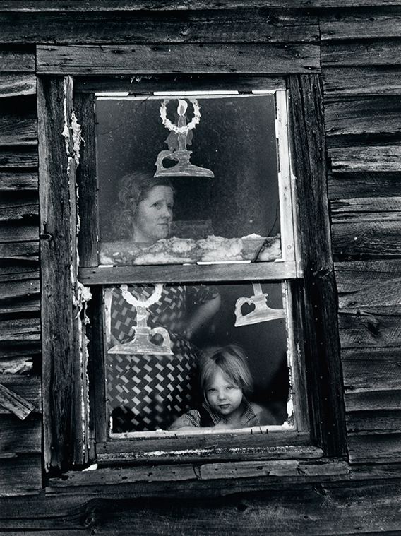 Arthur Weinstein's photograph, Wife and child of sub-marginal farmer at their window decorated for Christmas, Oswego County, New York
