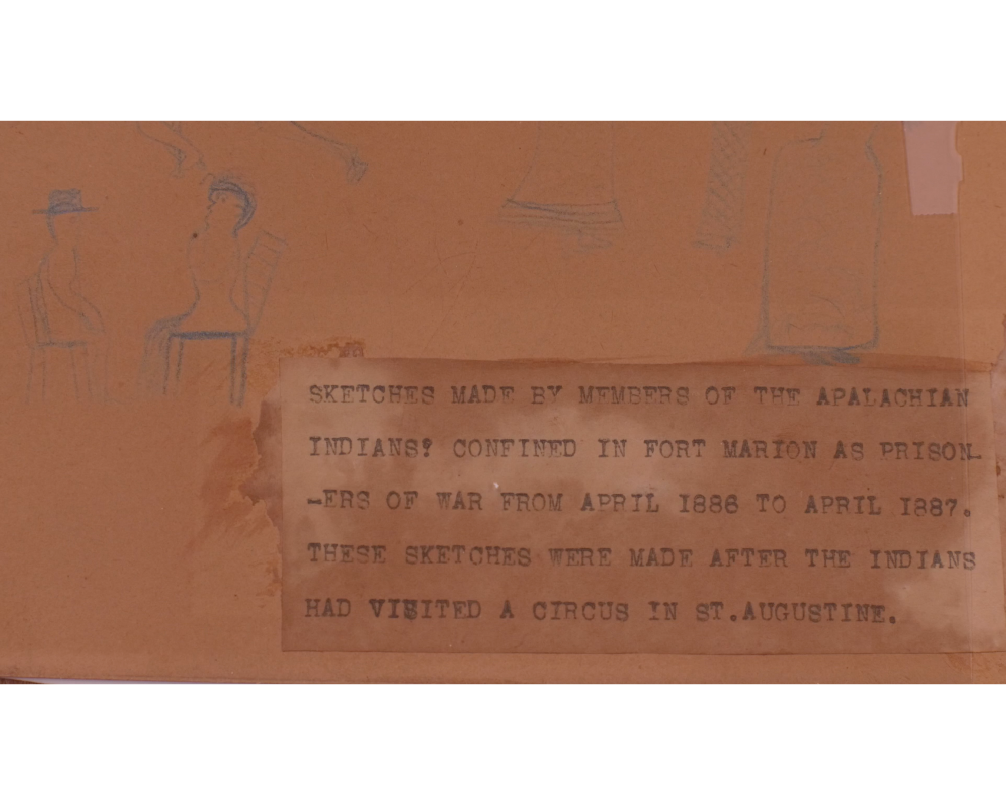 "Brown paper with sketch of two people seated at a table on the left with type-written text on right reading: ""SKETCHED MADE BY MEMBERS OF THE APALACHIAN [sic] INDIANS CONFINED IN FORT MARION AS PRISONERS OF WAR FROM APRIL 1886 TO APRIL 1887. THESE SKETCHES WERE MADE AFTER THE INDIANS HAD VISITED A CIRCUS IN ST. AUGUSTINE."""