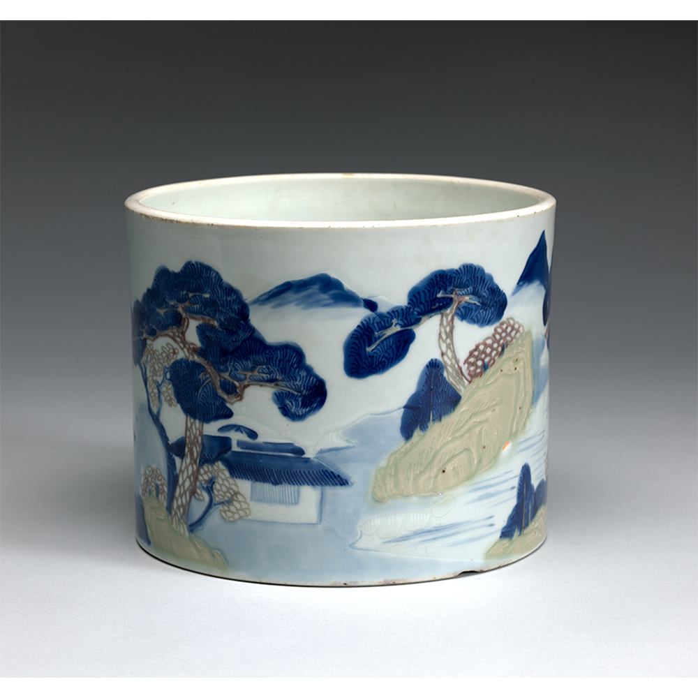 Small ceramic pot with pines, thatched huts, and fisherman painted on.