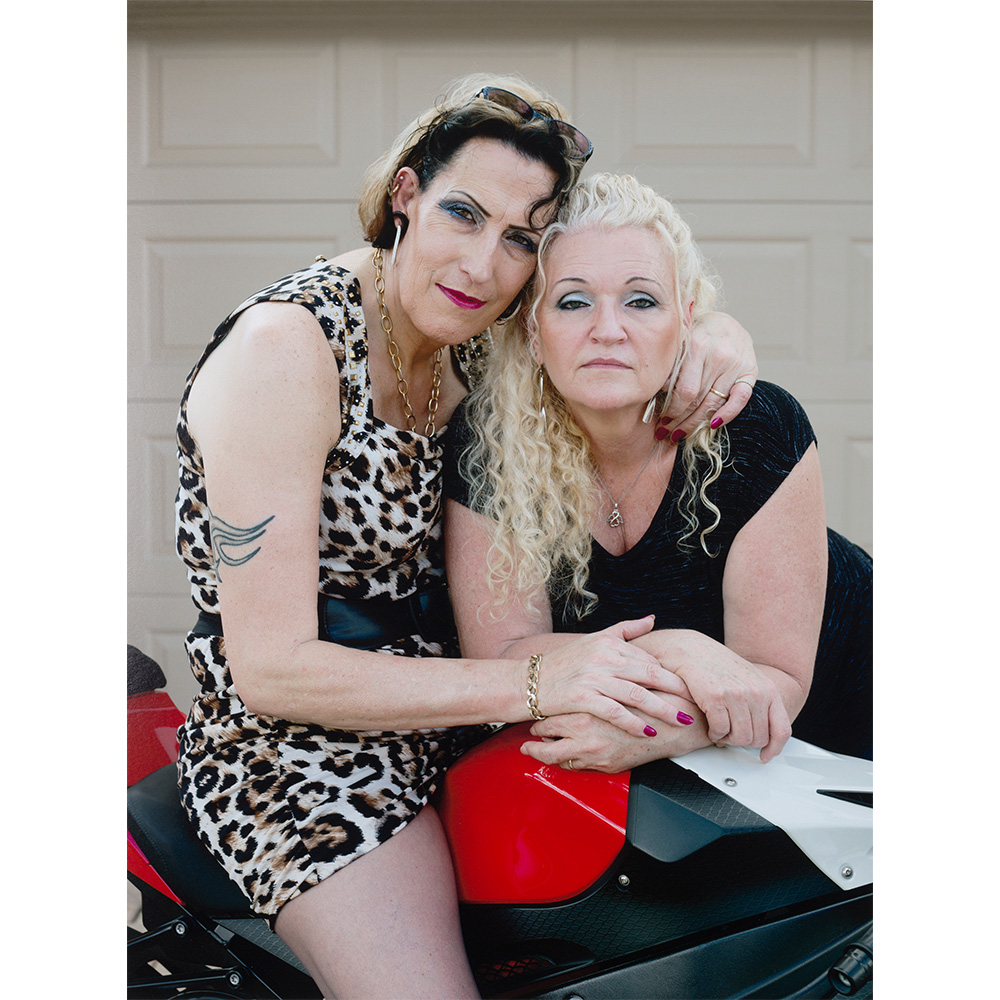 Photograph of two women, one sitting on a motorcycle wearing a dress.