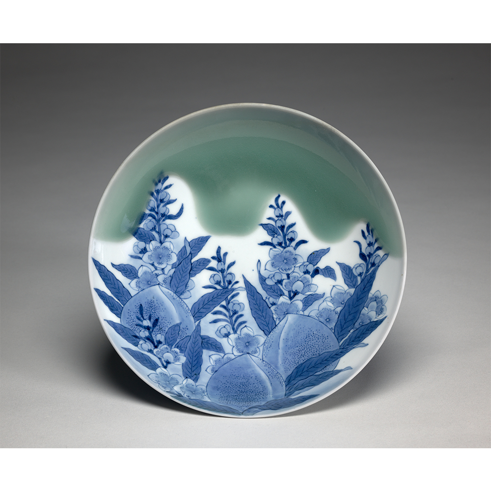 Plate sized dish with designs of peaches and bellflowers in blue and green.