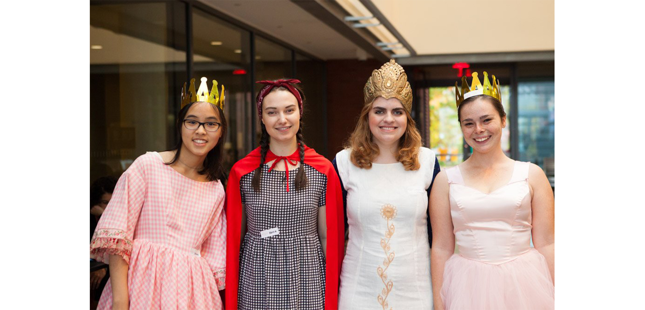 Four students with homemade crowns on in SCMA atrium