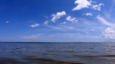 "Still from Hopinka's ""Cloudless Blue Egress of Summer"": slightly cloudy blue sky filling top of frame with ocean water below the horizon line."