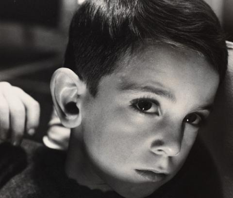 Photo portrait of a young white boy. His head is turned down but he looks up at the camera. A shadow crosses his face.