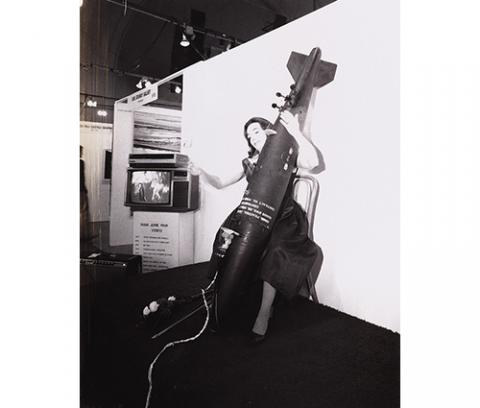 black and white image of woman playing a cello shaped like a bomb in front of a white wall with a video monitor to her right